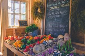 fresh veggies stand with prices on a chalkboard